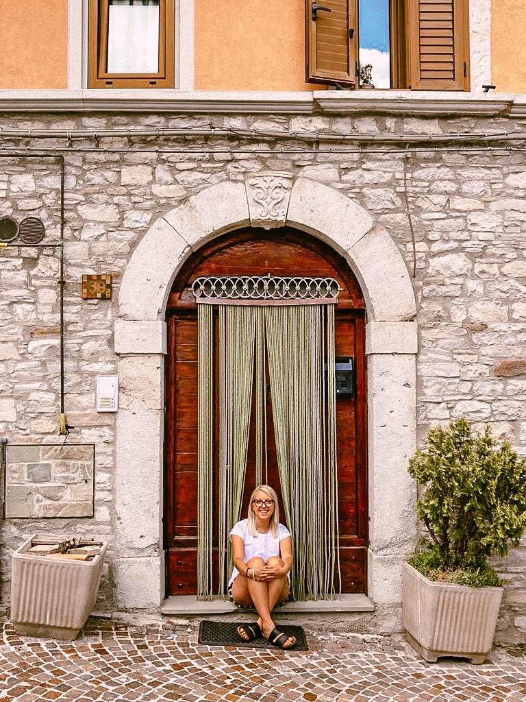 Ragazza seduta di fronte ad una porta ad Agnone