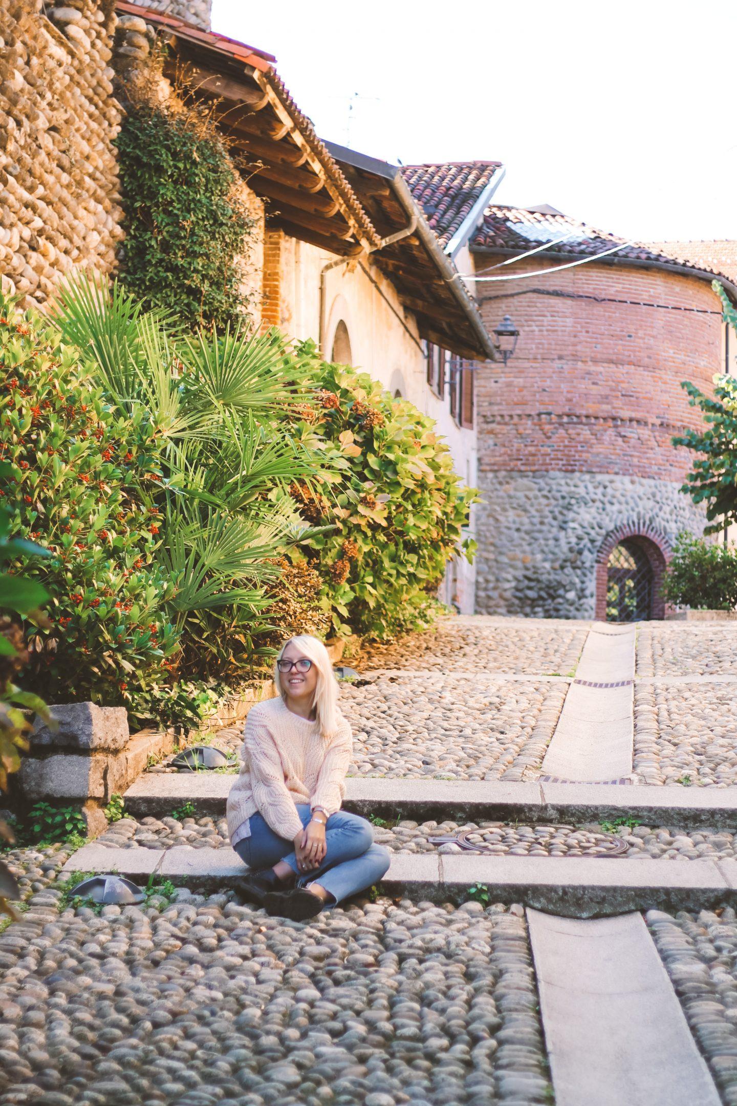 Ragazza seduta su un ciottolato in un borgo
